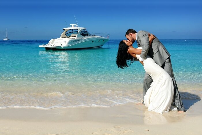 A couple kissing on a beach on their honeymoon in cayman islands