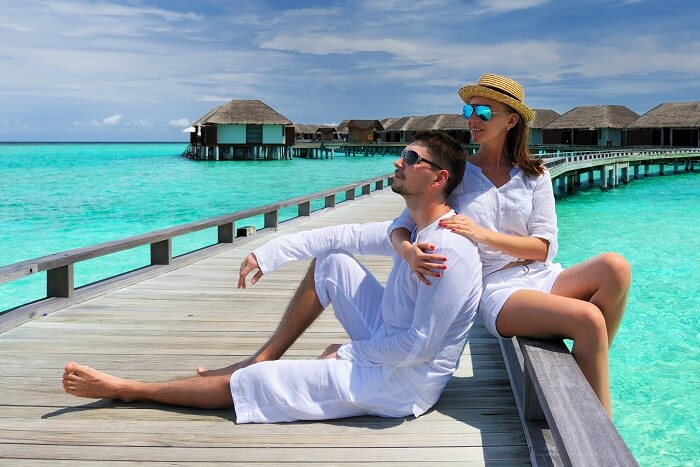 A couple on a jetty in front of the overwater properties on an island resort in Maldives
