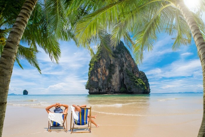 A couple relaxes on a beach in the Phang Nga Bay on one of the best islands in Thailand for honeymoon