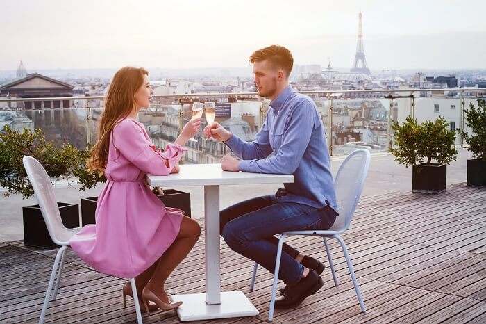 A couple drinking champagne at a luxury rooftop restaurant in Paris on their gourmet honeymoon