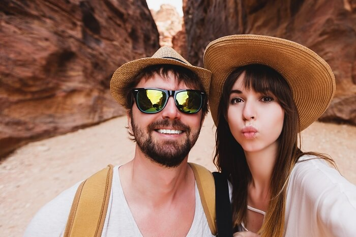 Young couple taking selfie at the canyon on their honeymoon in Jordan