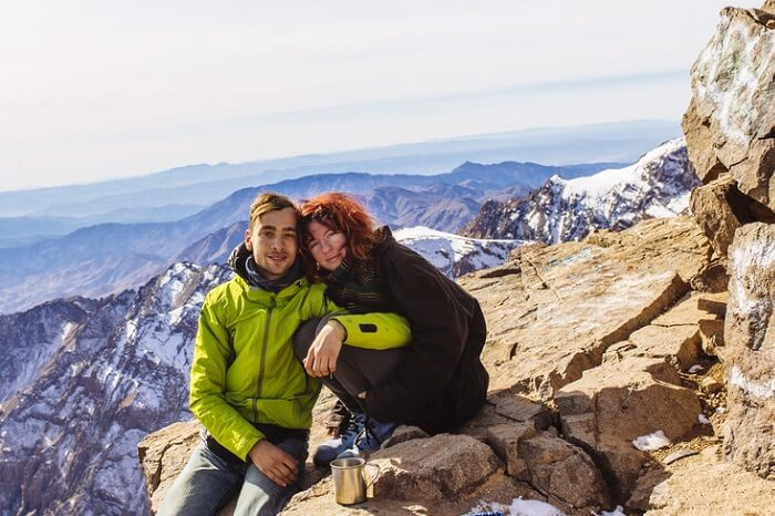 A couple sitting in the mountains of Toubkal in High Atlas mountain area durng their honeymoon in Morocco