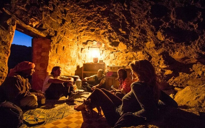tourists living inside a dimly lit cave with Bedouin people