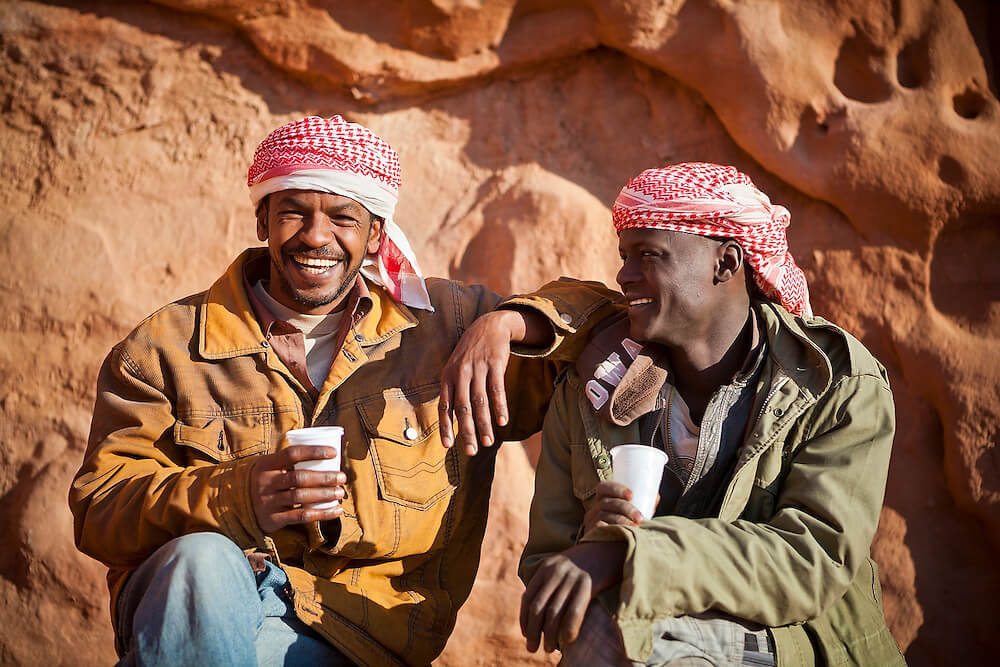 two Bedouin guys drinking tea laughing