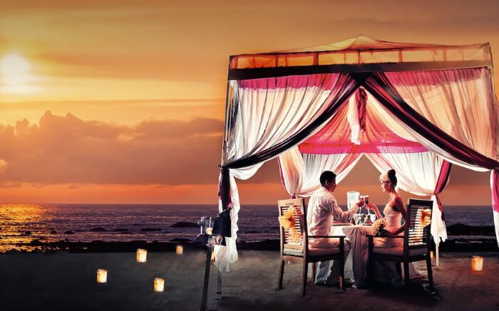 A couple having a romantic dinner in a tent on Kuta Beach