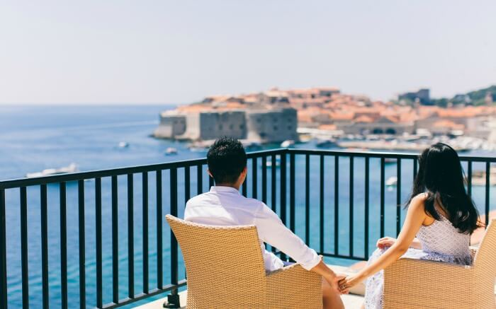 A couple sitting on a balcony with sea view