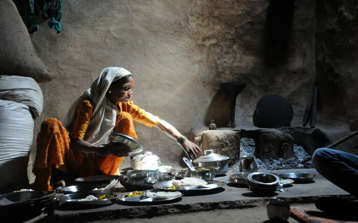A local village woman cooking traditional food for tourists in Purushwadi
