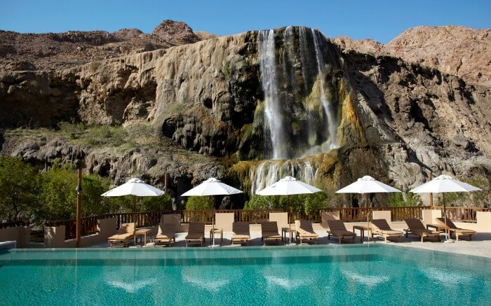 A pool and sun decks with hot spring waterfalls in the background