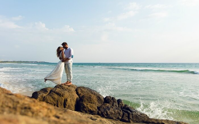 Couple kissing on a cliff by the sea shore in Sri Lanka