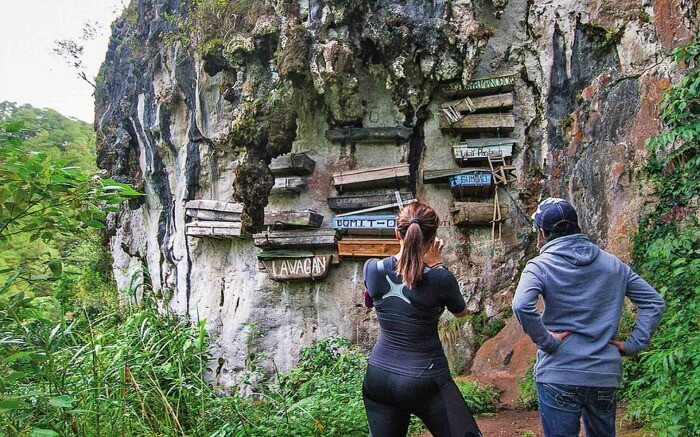 Couple looking at hanging coffins in Sagada Mountain Province in Philippines