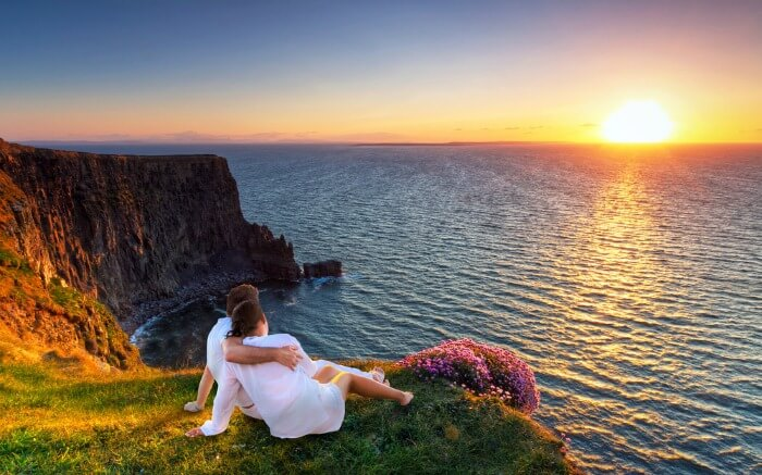 Couple relaxing on a cliff savoring the sunrise view in Ireland