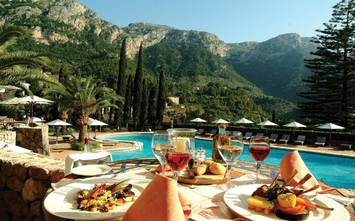 Food served on a table by a pool overlooking mountains in Mallorca