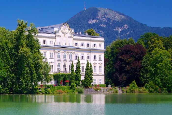 A beautiful hotel by a lake with mountain background
