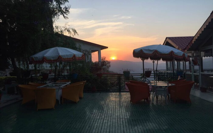 Seating area of Maple Resort overlooking a setting sun in Chail