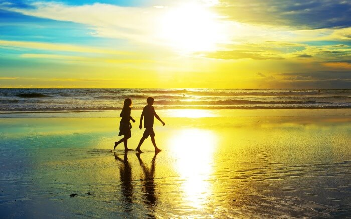 Silhouette of a couple walking on Kuta Beach during sunset
