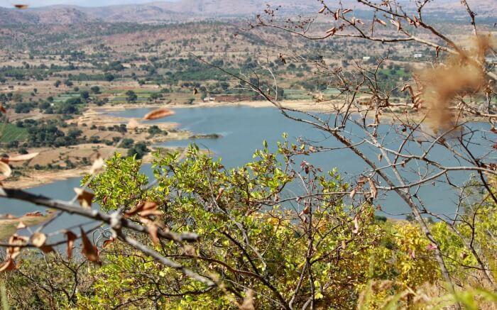 a cliff overlooking a lake and hills in Makalidurga