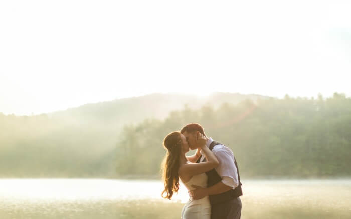 a couple kissing each other as the sun shines in the background
