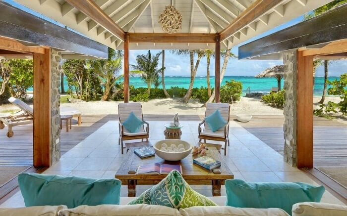 a large cabana with comfortable chairs on the beach