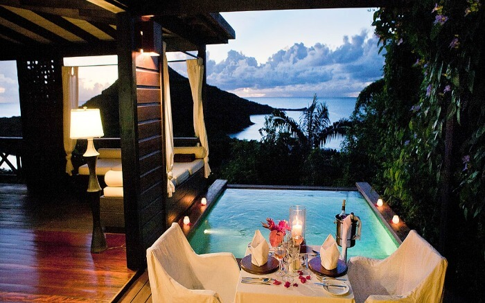 a romantic dining setting beside a pool overlooking the sea