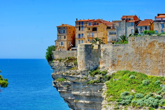 Colorful houses located atop the limestone cliff in Corsica