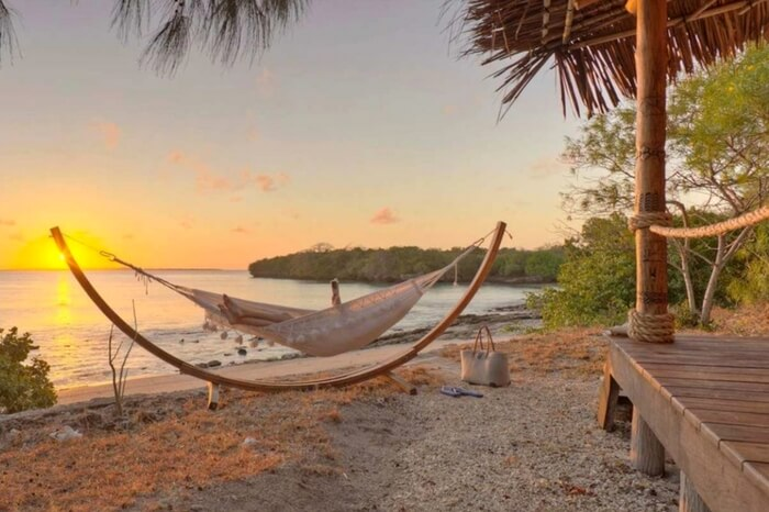 A woman relaxing by the beach in a hammock on a Mozambique Island