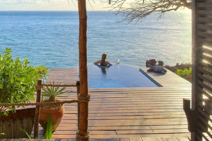 A woman looking at the ocean while relaxing in an infinity pool in a lodge in Mozambique