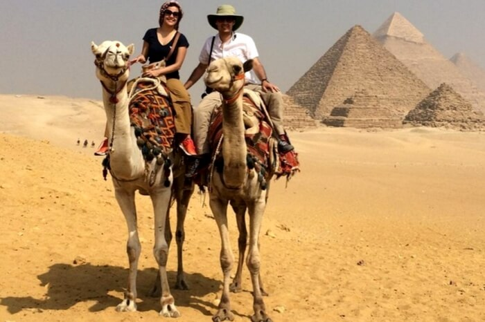 Couple enjoying a camel ride near Pyramids in Egypt