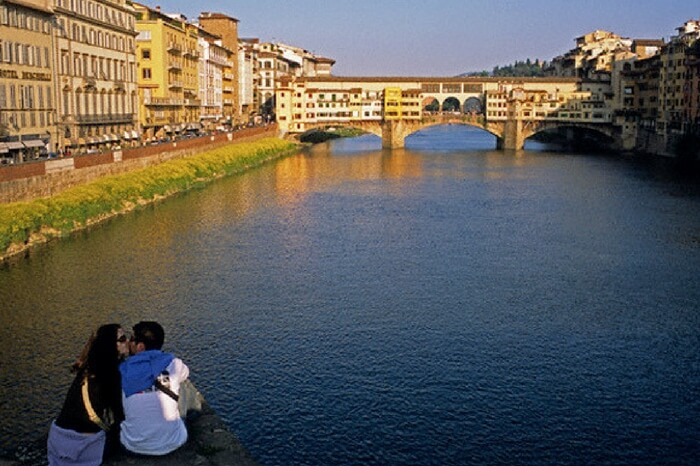 Couple kissing on the bank of a river in Siena