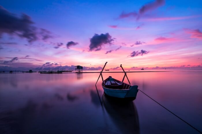 A boat docked by the sea shore in Vietnam at sunrise