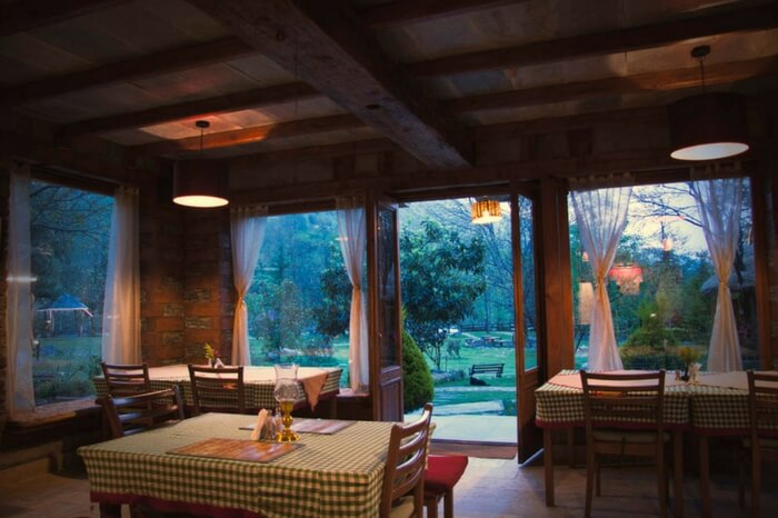 A view of dining space of Neeralaya Hotel overlooking garden area in Manali