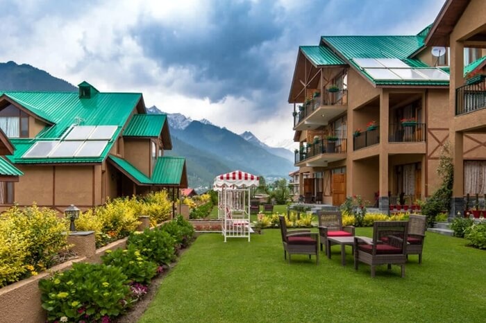 A view of cottages of Anantmaya Resort with mountains in the backdrop