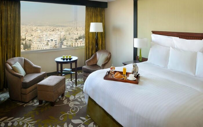 breakfast tray on a hotel bed and a window offering city views