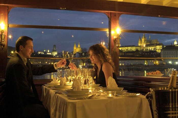A couple enjoys a romantic dinner while cruising in the canals of Prague