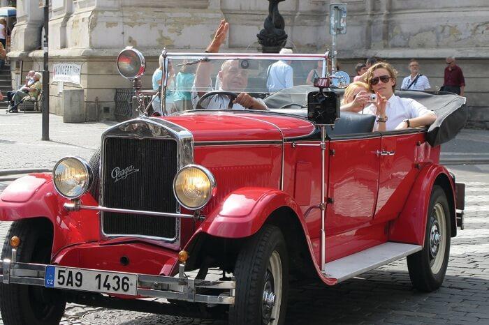 A couple takes a vintage car tour on their honeymoon in Prague