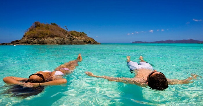 A couple swimming in the Caribbean waters at Trunk Bay in US Virgin Islands
