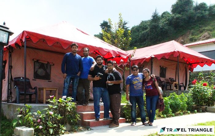A bunch of travelers pose for a photgraph outside their tents in Chakrata