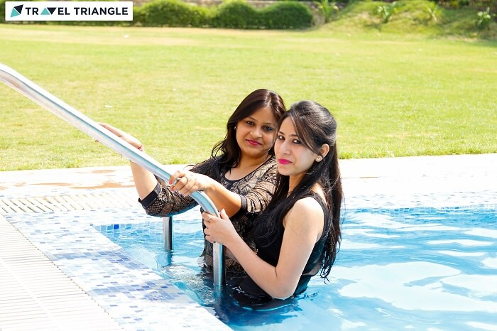 Two girls enjoying in a swimming pool at a resort in Jim Corbett