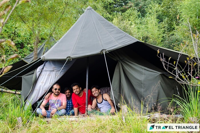 A group posing from the tent at the campsite of Mukteshwar