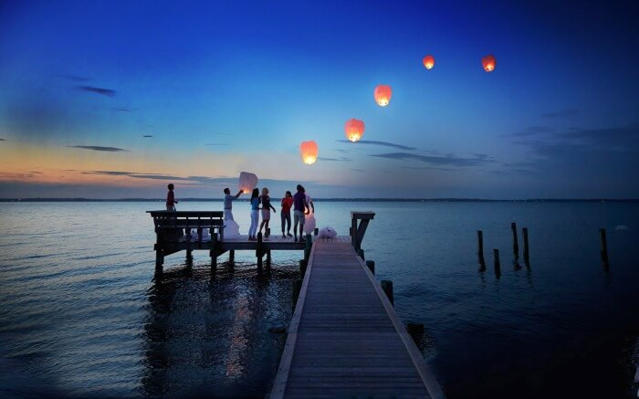 people releasing floating lanterns from a pier