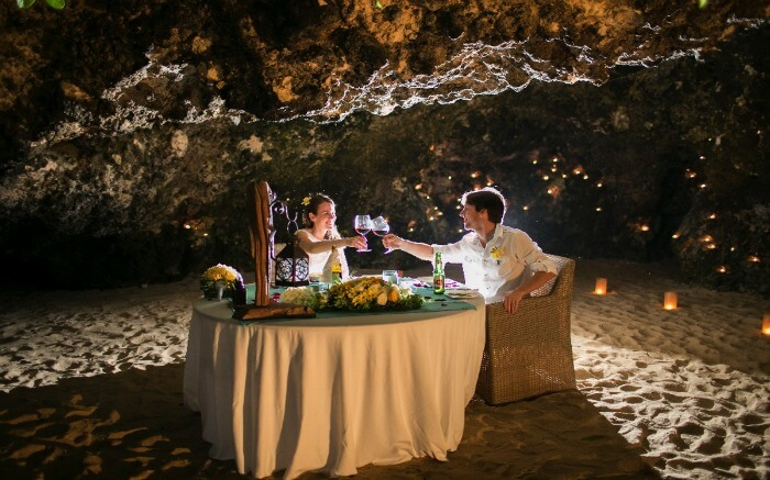A couple having a romantic dinner in a romantic cave