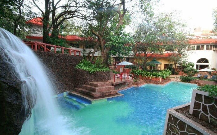 A fountain gushing into the pool of Horseland Hotel & Mountain Spa in Matheran