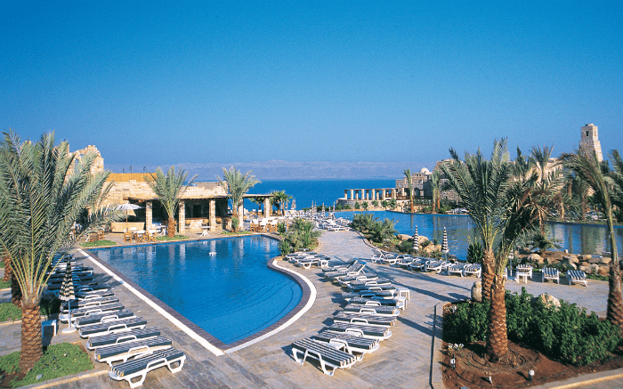 A great view of greenery surrounding the pool area of Moevenpick Resort & Spa Dead Sea overlooking the Dead Sea
