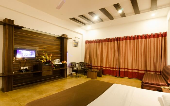 A hotel room with wooden decor and a huge window covered by curtains