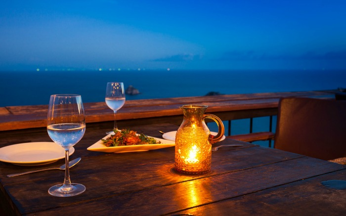 A romantic candlelit dinner table overlooking the sea