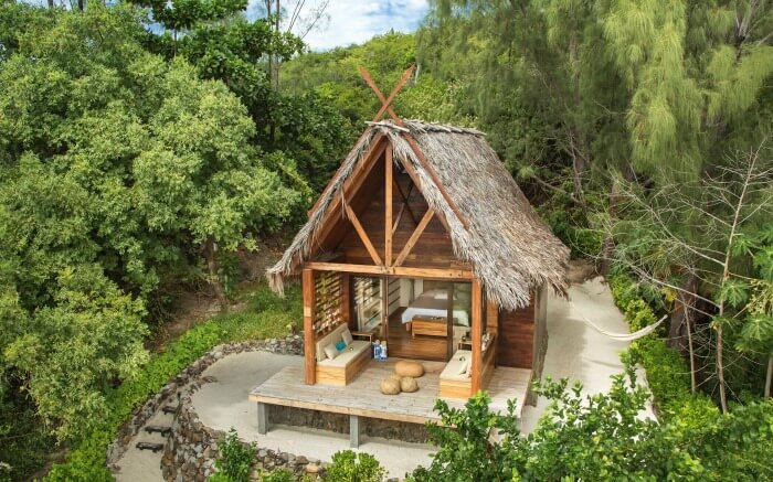 A thatched bungalow surrounded by lush greenery in Tsarabanjina in Madagascar