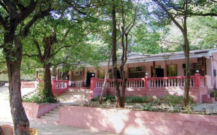A view of Adamo The Village Hotel in Matheran nestled in trees