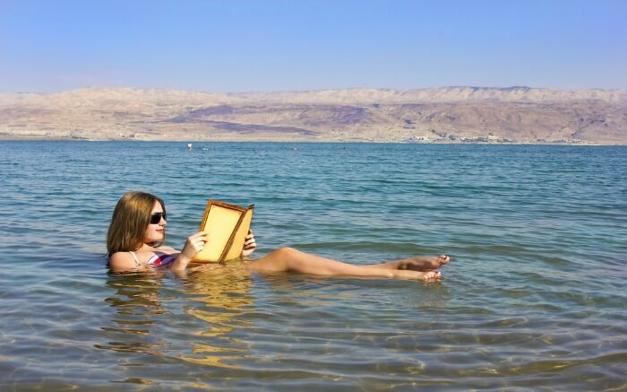 A woman reading a book in Dead Sea in Jordan