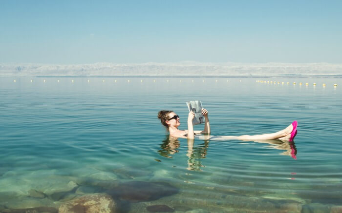 A woman reading newspaper while floating on the waters of Dead Sea