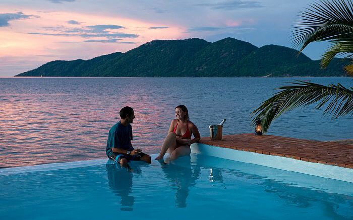 Couple spending a leisure moment in an infinity pool in Madagascar