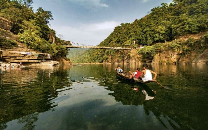 Kids rowing a boat in a river of Meghalaya